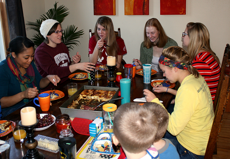 College students eating a meal together at Steve and Liz Arnold's home